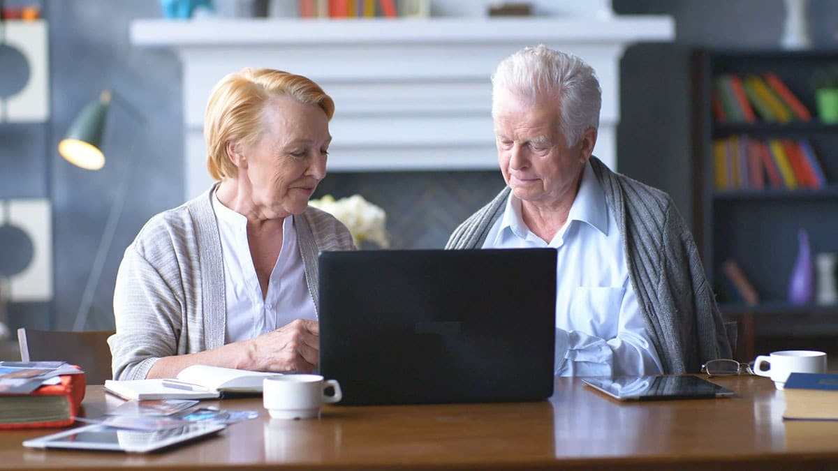 enior-couple-websurfing-on-internet-with-laptop-happy-elderly-man-and-woman-using-computer